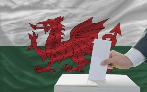 man putting ballot in a box during elections in wales in front of flag